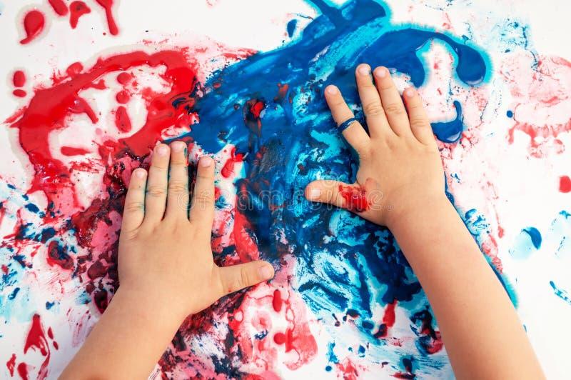 在乱糟糟的纸上涂上彩绘的手 免版税库存图片