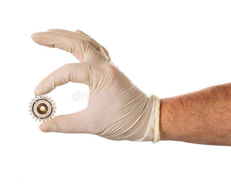 在乳汁手套的手与使用的齿轮 免版税库存图片