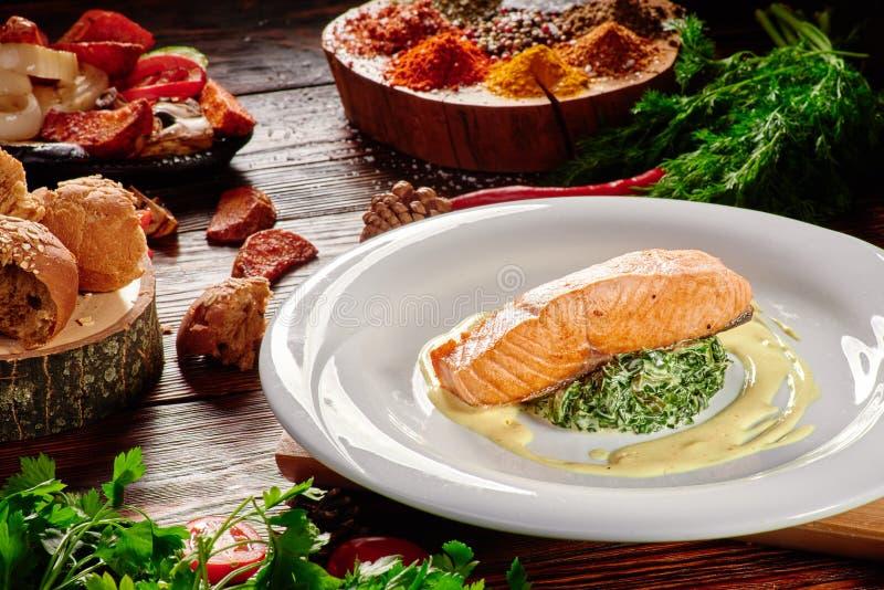 在乳脂状的调味汁的盘三文鱼内圆角用在白色板材的菠菜在黑暗的木背景 免版税图库摄影