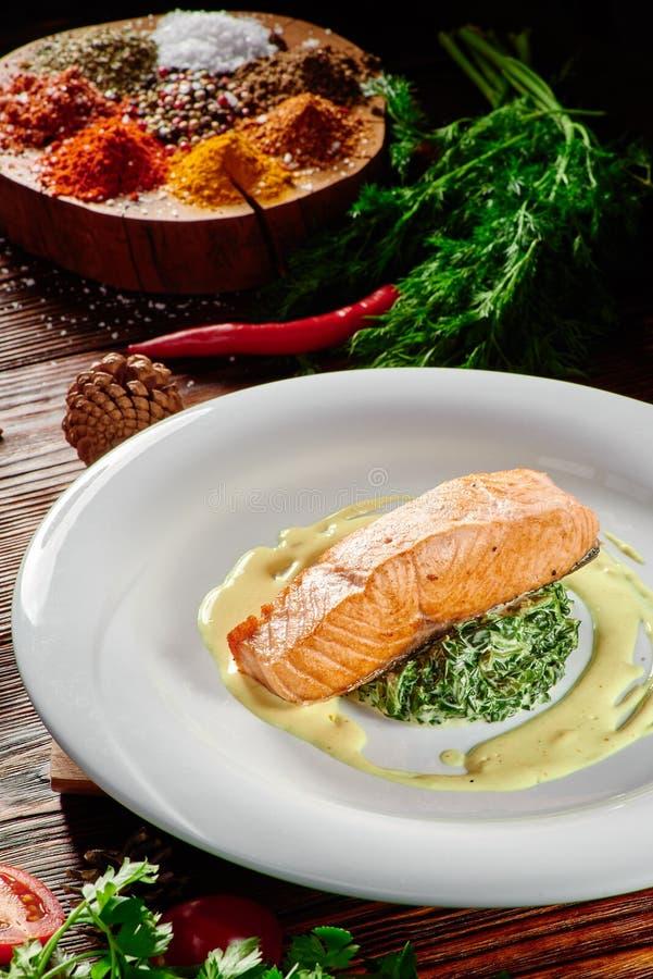 在乳脂状的调味汁的盘三文鱼内圆角用在白色板材的菠菜在黑暗的木背景 库存照片
