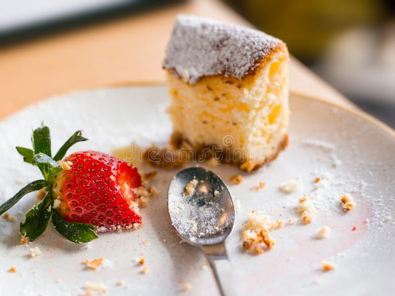 在乳酪蛋糕的左边用在棕色背景,选择聚焦的草莓 免版税图库摄影