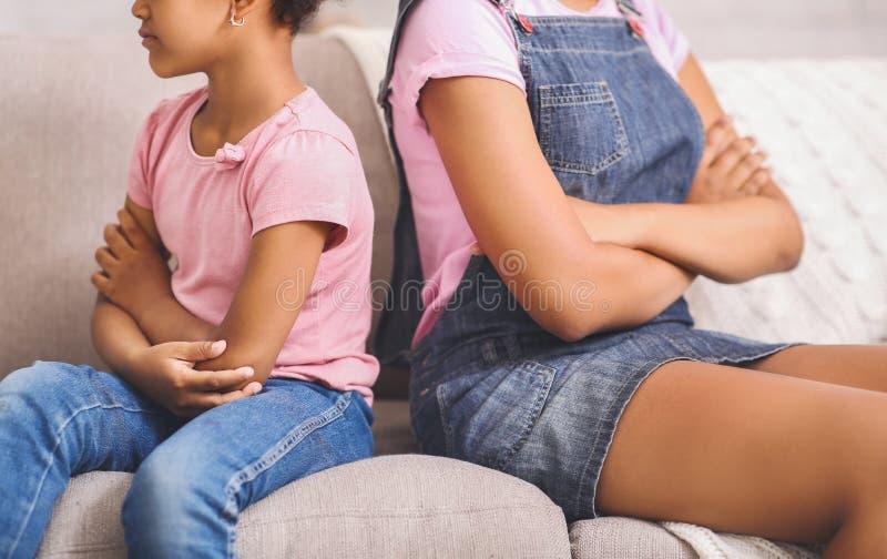 在争吵以后的非裔美国人的姐妹,紧接坐长沙发 免版税库存照片