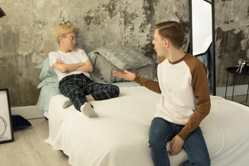 在争吵的年轻国际快乐夫妇在家在卧室 库存图片