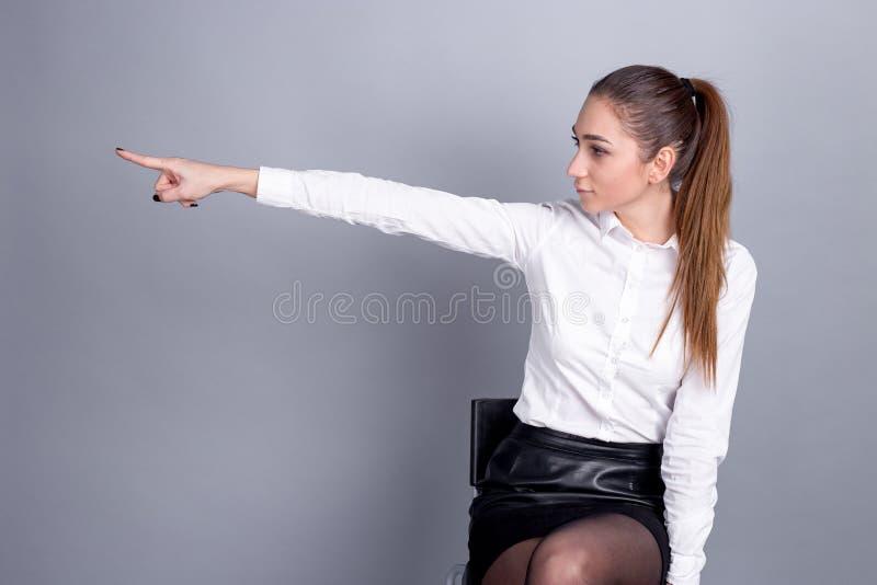 在事务的妇女上司 指示在工作 女孩显示一个手指 库存图片