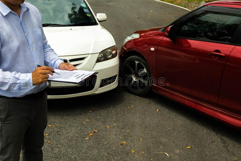 在事故以后的保险代理公司审查的汽车在路 在 免版税库存图片