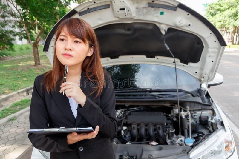 在事故以后的保险代理公司审查的汽车,拿着笔和 免版税图库摄影