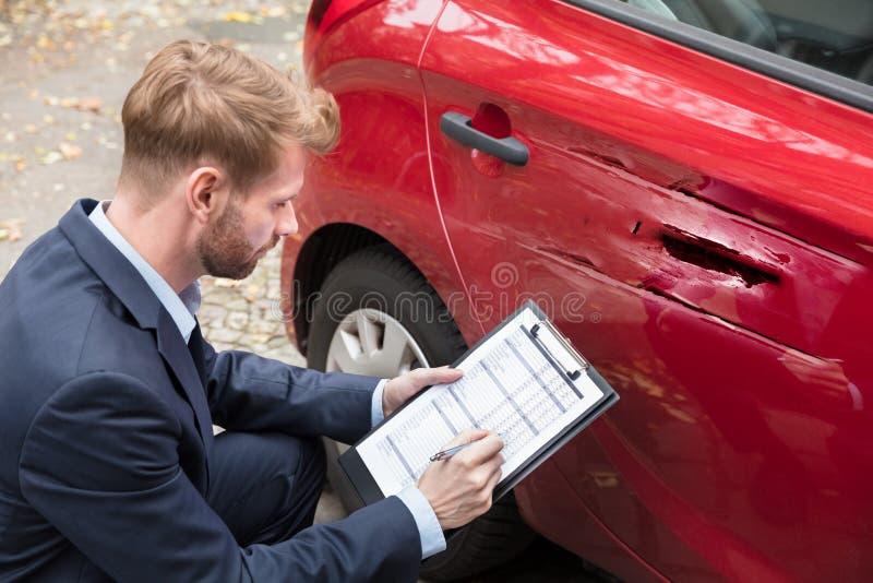 在事故以后的保险代理公司审查的汽车 图库摄影