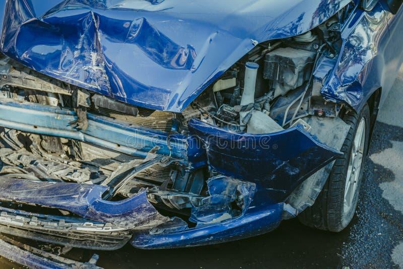 在事故以后的被碰撞的蓝色汽车在街道上 库存照片