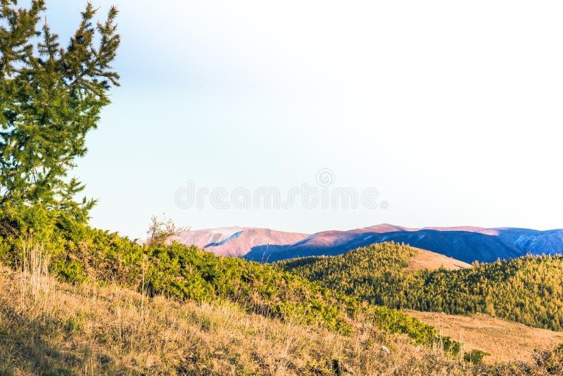 在云彩、岩石峰顶和小山下的山脉在蓝天下 免版税库存照片