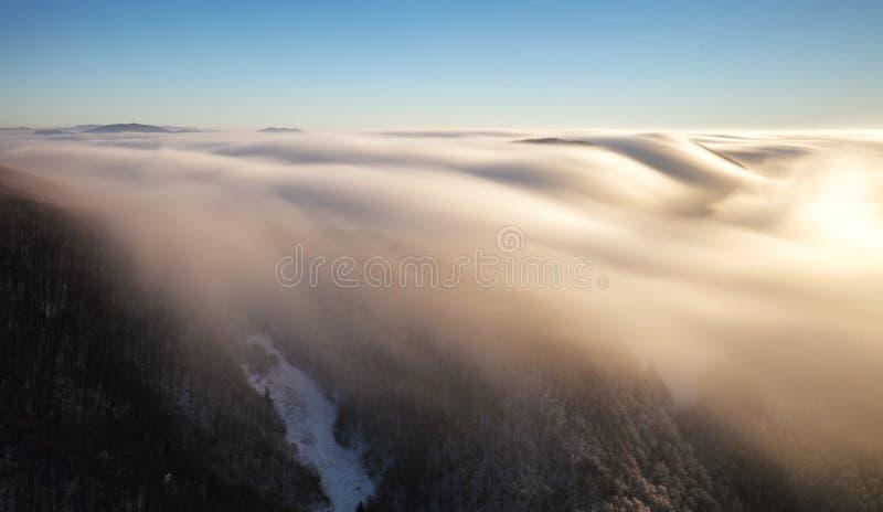 在云彩上在冬天-在日落的山landcape,斯洛伐克 图库摄影