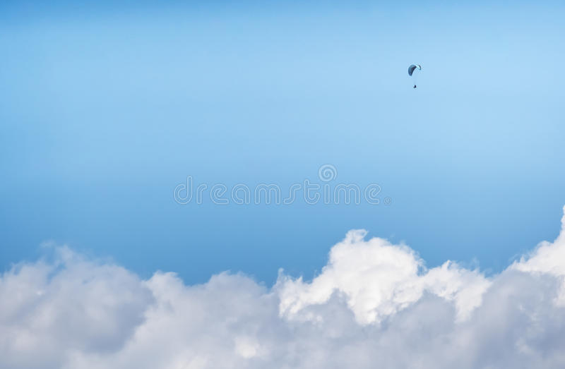 在云彩上的孤独的滑翔伞飞行员 免版税库存图片