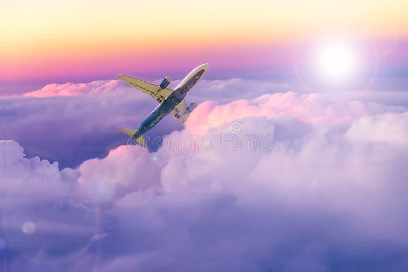 在云彩上的美丽的日落天空与向上移动的飞机 旅游业和旅行图象 库存照片