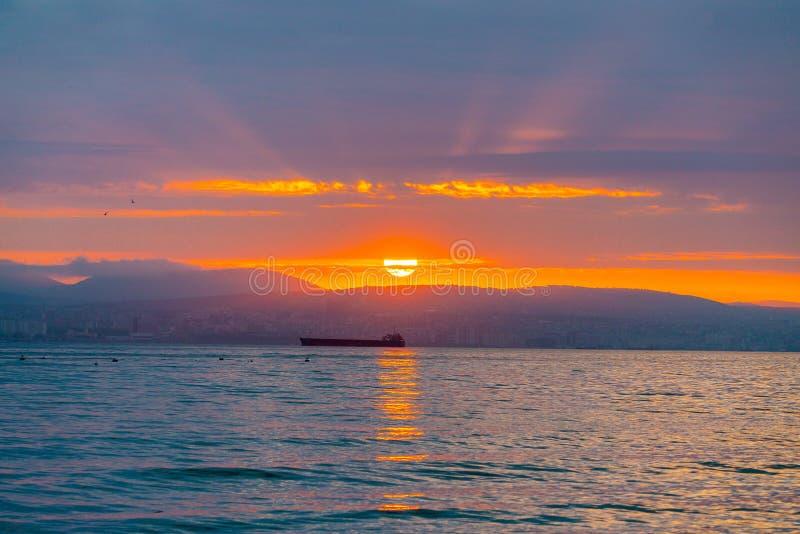 在云彩中的美好的日落 太阳光芒完全美好 城市、山和船在海 库存图片