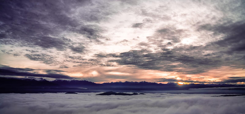 在云彩之间的日出在喜马拉雅山 免版税库存照片