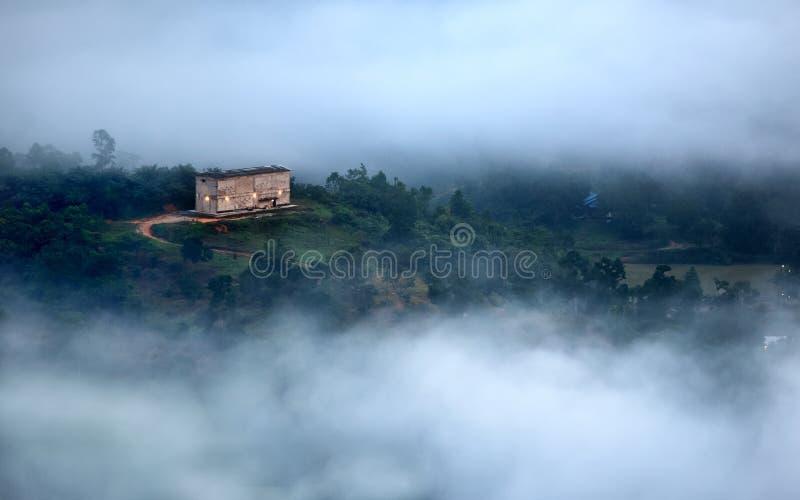在云彩内掩藏的遥远的房子 免版税库存照片