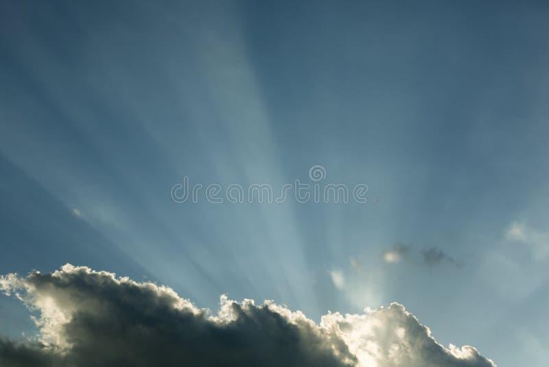 在云彩后的太阳光芒 免版税库存照片