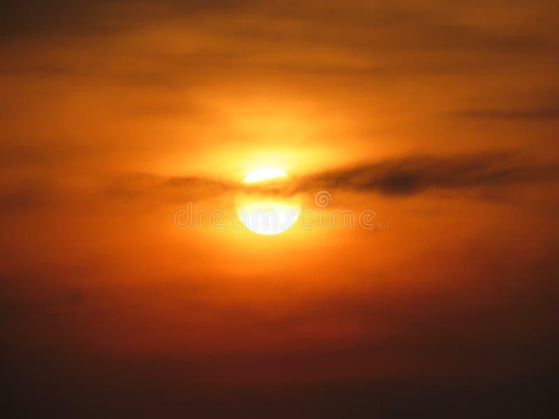 在云彩后的太阳在日落期间 免版税库存照片