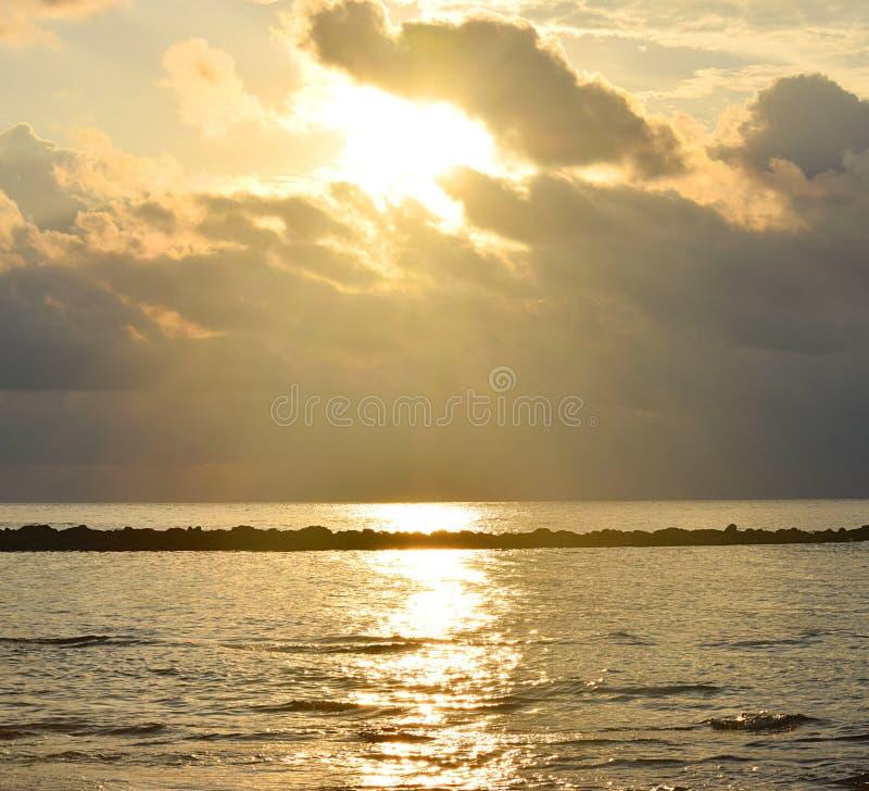 在云彩和光束后的明亮的金黄黄色阳光的太阳,反射在海水的,乌云和温暖的颜色在天空 免版税库存照片