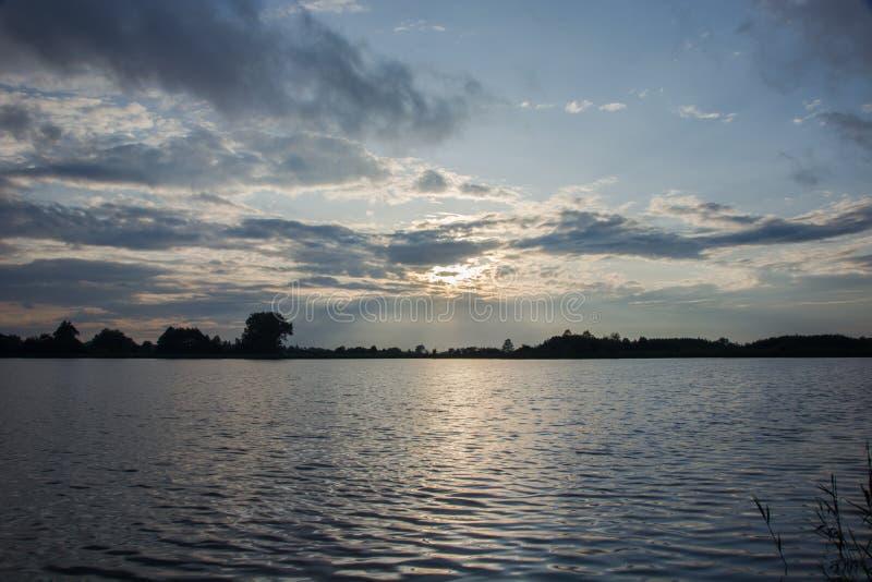 在云彩和反射的光后的太阳在湖的水中 免版税库存图片