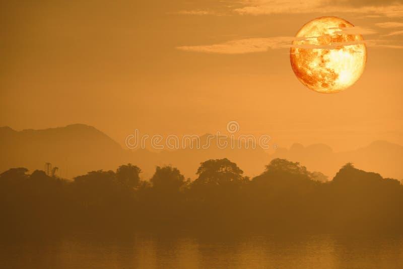 在云彩和山的超级血液鱼月亮后面在夜空 免版税库存照片