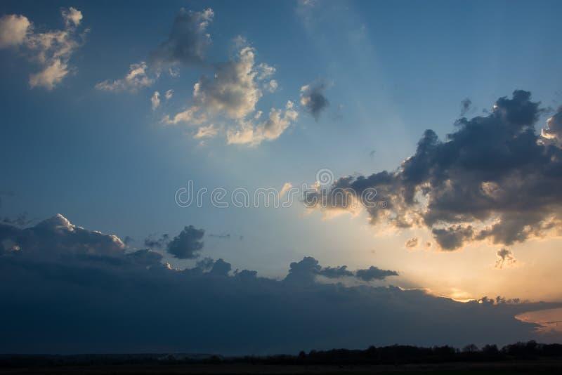 在云彩和阳光后的太阳设置在天际和五颜六色的天空上 库存照片