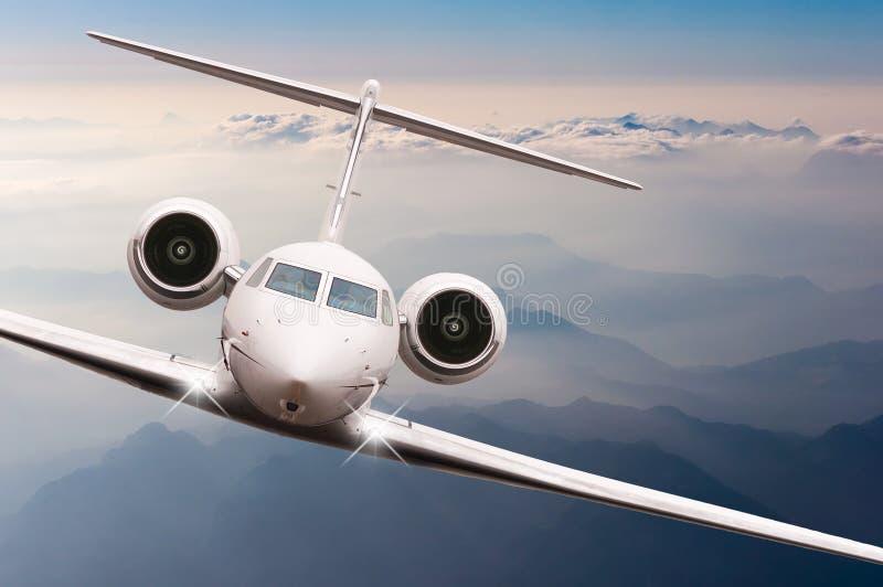 在云彩和阿尔卑斯山的飞机飞行在日落 一个大乘客或货物航空器,企业喷气机的正面图 库存照片