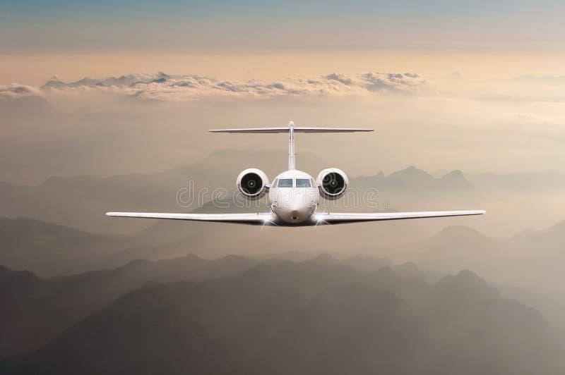 在云彩和阿尔卑斯山的飞机飞行在日落 一个大乘客或货物航空器,企业喷气机的正面图 免版税库存图片