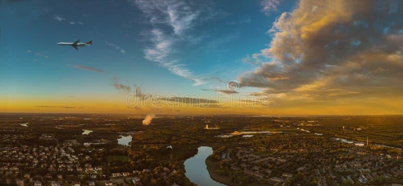 在云彩的五颜六色的日落飞机在城市 免版税库存图片