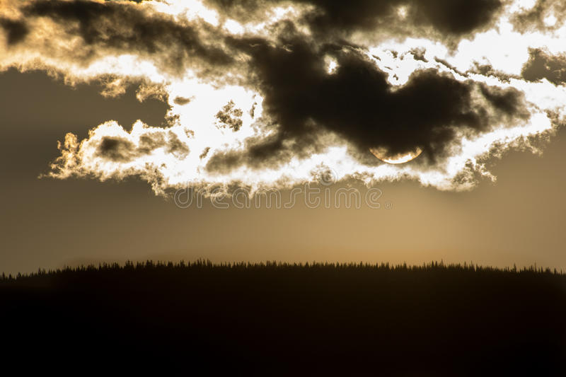 在云彩的日落在小山 库存图片