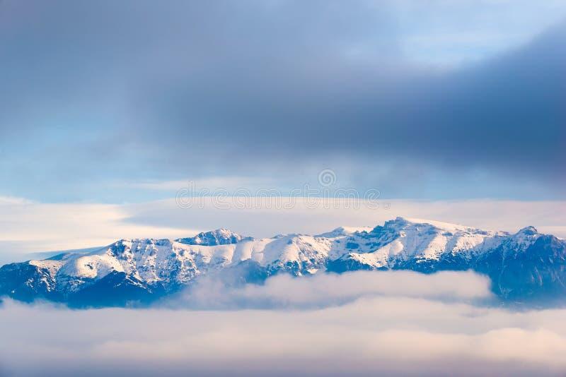 在云彩的雪报道的陡峭的山峰的美好的风景 免版税库存图片
