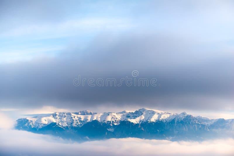 在云彩的雪报道的陡峭的山峰的美好的风景 免版税库存照片