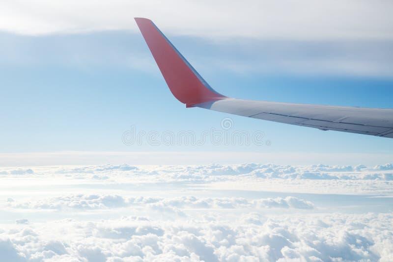 在云彩的鸟瞰图和飞机在蓝天飞过 免版税库存照片