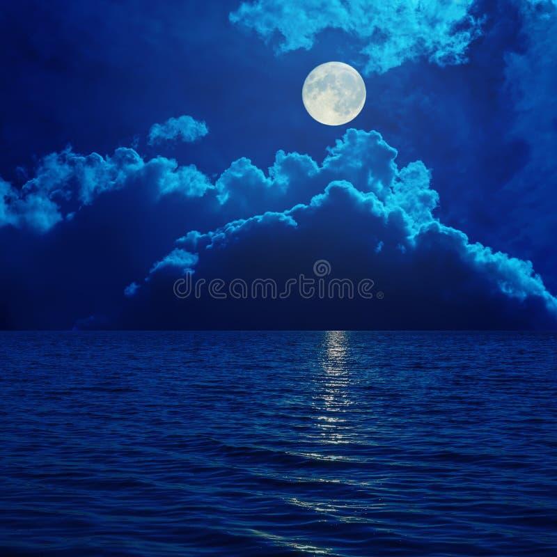 在云彩的满月在海 免版税库存图片