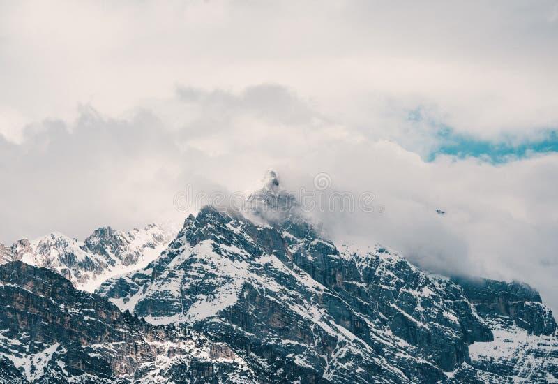 在云彩盖的美丽的岩石多雪的山空中射击  免版税库存照片