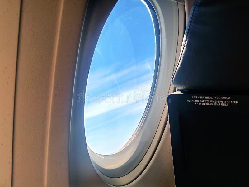 在云彩视图上的飞机飞行从与蓝天的窗口 库存照片