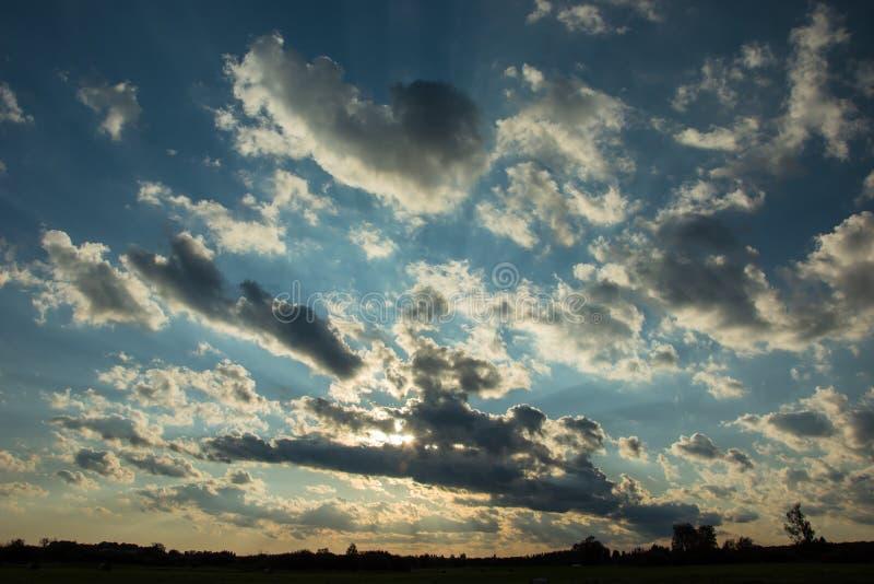 在云彩,光束,白色和灰色云彩后的太阳在天空 免版税库存图片
