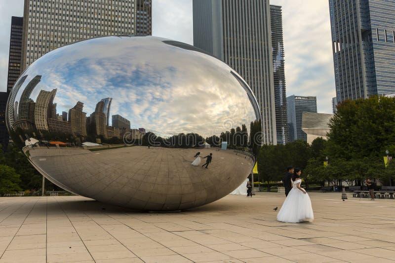 在云门Anish Kapoor雕塑被拍摄的亚洲婚礼夫妇侧视图,芝加哥前面 免版税库存照片