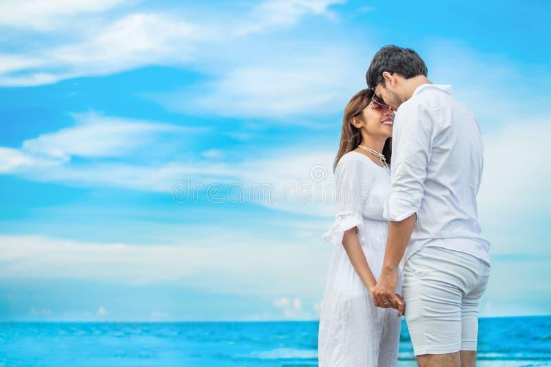 在互相看和结合在一起使手的爱的年轻夫妇在天空蔚蓝的海海滩 愉快的微笑的年轻婚礼与 库存照片
