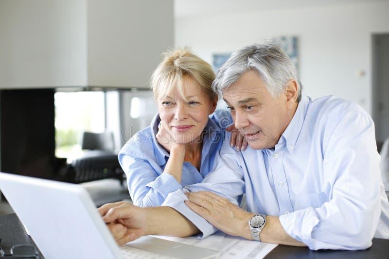在互联网上连接的资深夫妇 免版税库存照片