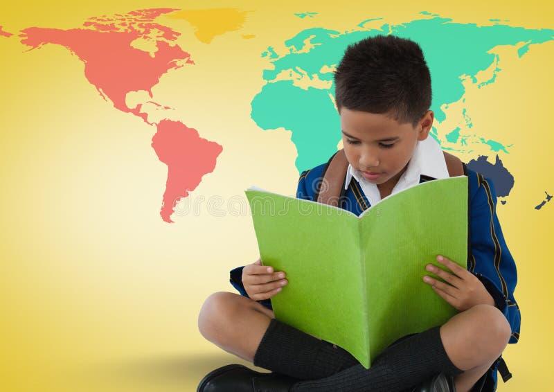 在五颜六色的世界地图前面的男小学生读书 库存照片