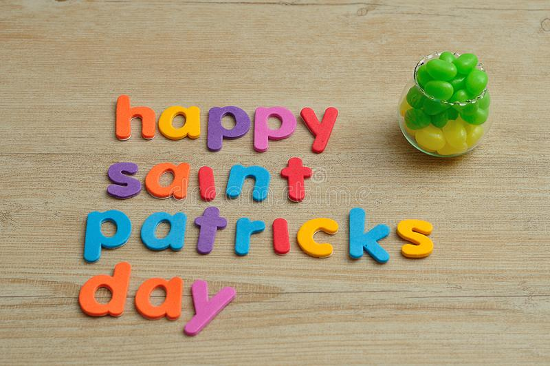 在五颜六色的信件的愉快的圣徒Patricks天与罐用绿色和黄色软心豆粒糖填装了 库存照片