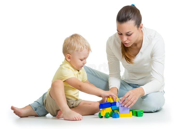在五颜六色的塑料块外面的母亲和孩子修造 家庭和童年概念 免版税库存图片