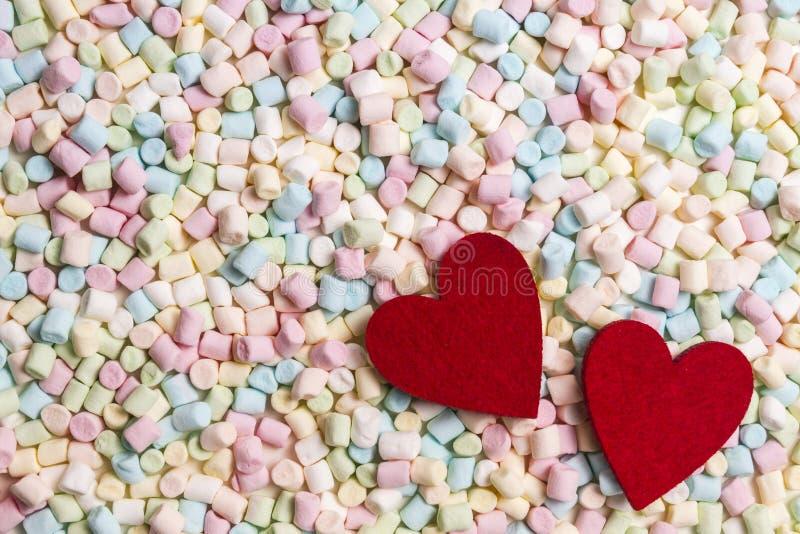 在五颜六色的微型蛋白软糖背景的两红色心脏 免版税库存照片