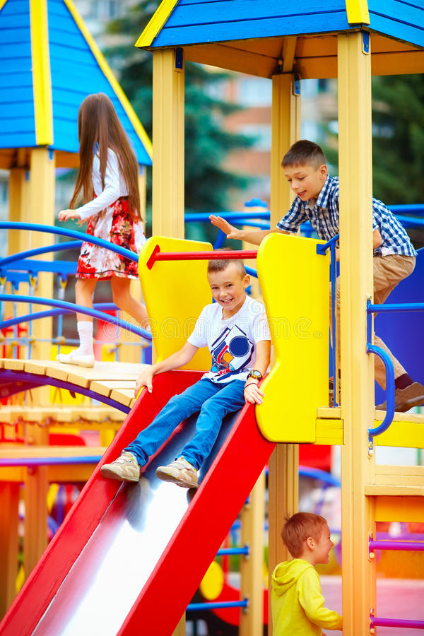 滑在五颜六色的操场的小组愉快的孩子 免版税库存图片