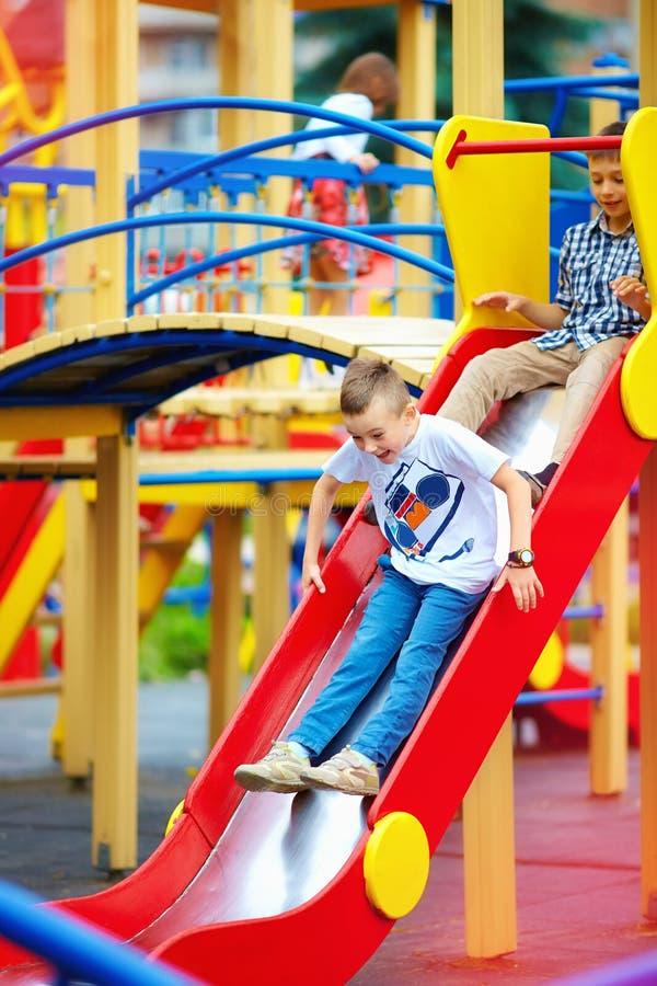 滑在五颜六色的操场的小组愉快的孩子 库存照片