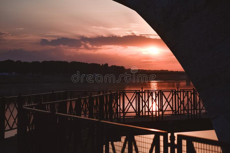 在五颜六色的日落背后照明的河沿步行 免版税库存图片
