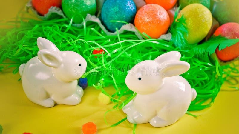 在五颜六色的明亮的鸡蛋附近的两只白色porctlain兔子 库存图片