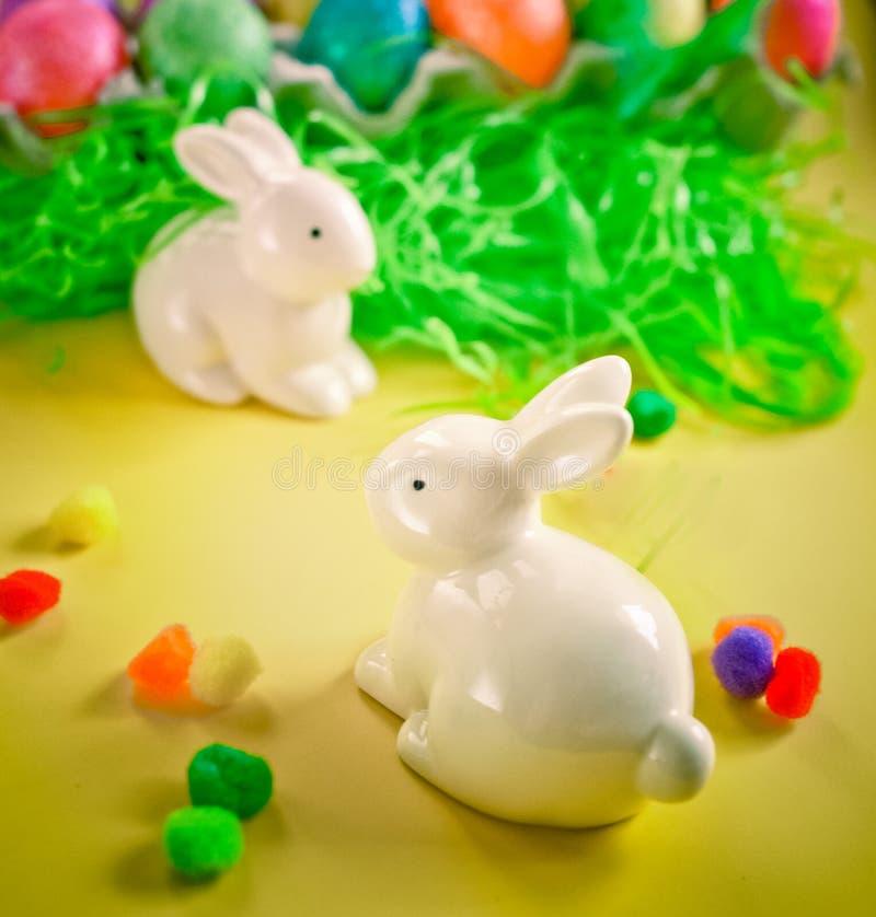 在五颜六色的明亮的鸡蛋附近的两只白色porctlain兔子 库存照片
