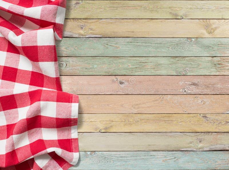 在五颜六色的木桌上的红色方格的野餐桌布 免版税库存照片