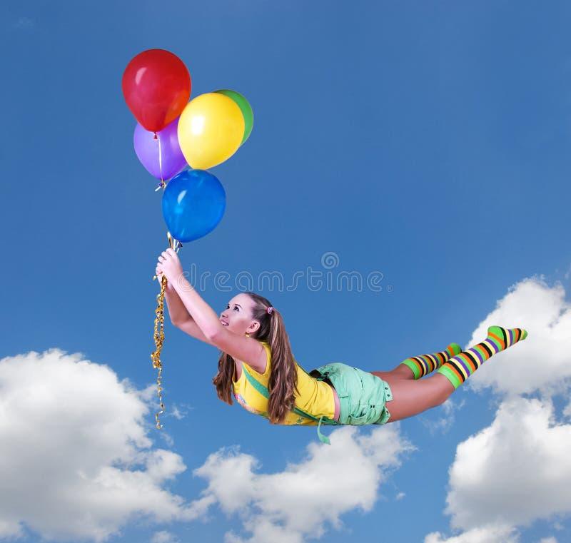 在五颜六色的气球的年轻俏丽的女孩飞行在蓝天 免版税图库摄影